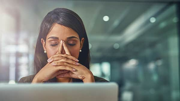 woman with eyes closed and laptop open